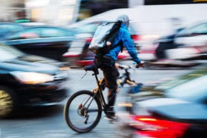 Man riding a bicycle with blurred cars in the background