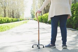 Elderly woman walking in the park with a cane
